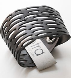 Otra 300 Km Cuff    Otra jewelry is made from bicycle inner tubes. The added value is provided by the unique nature of the products and the manual work required for the development of these products. Treating waste as raw material is a way to recycle and serves as a sustainable development approach. Made in Canada. Size: 15 cm wide x 6 cm high.