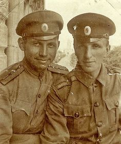 Imperial Russian Army - Ensigns (NCO) with epaulette patterns of one centered star. Service badges on epaulettes may be crossed cannons indicating both are artillery personnel. Oval cap badge visible. Note the differing symmetric tunics with small or large buttons. WW1.