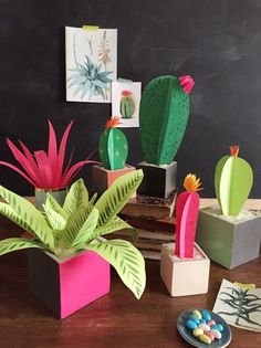 """If you haven't been blessed with a green thumb or even the ability to keep one houseplant alive, this DIY craft is for you!  Make bright plants out of paper with the help of scissors and paint. You can then """"plant"""" them inside of wooden boxes (as pictures above) or terra cotta pots."""