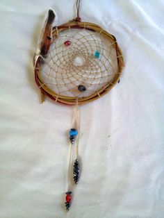 This Catcher is made of Red and Yellow willow, Glass, Magnet, and Wooden Beads, Sinew, and Duck and Pheasant feathers make up the web