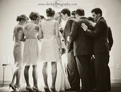 Wedding party praying over couple