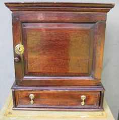 Originally designed for the storage of herbs and spices to stand on a table top, an expensive commodity of the time. Moulded cornice, below a moulded panel cupboard door having an interior of drawers and central pigeon hole for the mortar and pestle. The cabinet also has a long drawer to the base . Good original condition and good colour.