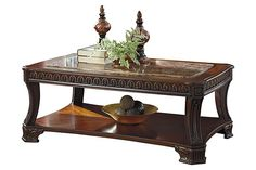 """The Ledelle Coffee Table from Ashley Furniture HomeStore (AFHS.com). The """"Ledelle"""" accent table collection beautifully captures the essence of rich Old World design with the traditional dark cherry stain finish flowing over the ornate detailing elegantly displayed along the legs, feet and apron topped with the sophisticated look of the beveled inserts print marble pattern finished in polyurethane."""