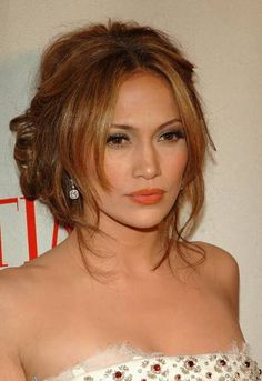 Jennifer Lopez shows off this soft updo that is loosely pulled back with a center part. Her bangs/fringe area are allowed to fall softly forward to frame her face. The back is fun and messy.