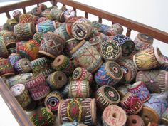 Untitled cradle full of wrapped and stitched wooden spools.