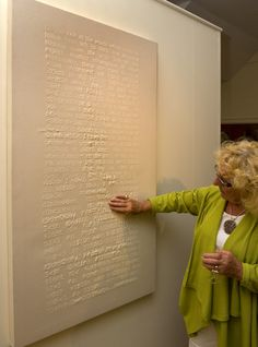 Tactile art. Image description: a woman in a gallery is touching the surface of a large white canvas, which has words and symbols in tactile raised print.