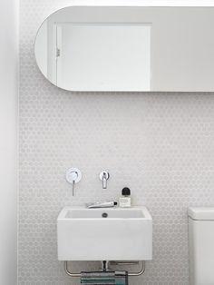 White minimalist bathroom with oval edged mirror and white #hexagonal tiles , designer Hugh Campbell. Borda oval de espelho e pastilhas brancas em lavabo.