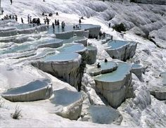 """Pamukkale (""""cotton castle"""" in Turkish) is a natural site in Denizli Province, Turkey, containing hot springs and travertines, terraces of carbonate minerals left by the flowing water. People have bathed in its pools for thousands of years. So want to see this amazing natural structure."""