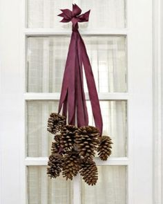You need 8 six-inch pine cones and 8 two-foot-long pieces of silk ribbon.     1. Use a glue gun and glue a cone to each ribbon. 2. Then collect all the ribbon ends and stagger them so that the cones fall nicely. 3. Tie together and hang on your door.