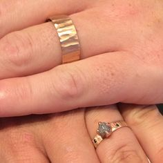 His and hers rose gold rings. Hers features a rough uncut grey diamond and inverted black diamonds.