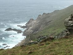 Lundy Island in late Spring - Visitors on rock promontary near Jenny's Cove looking back inland at puffins