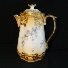 Delinieres & Co chocolate pot. Gilding follows the swirling decor, and includes a plewasing carmel coloring that fades to the glossy white background featuring the spray of baby blue and lavender flowers