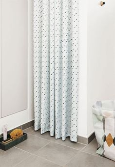 Shower curtain with a simple design. This mint coloured shower curtain from OYOY is super nice with its black polka dot print.