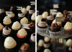 "An assortment of cupcakes with ""Yummy!"" flag cupcake toppers on a wedding dessert table."