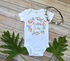 """""""Rainbow Baby"""" This is a very special bodysuit designed especially for that rainbow baby and the mommas that have suffered a pregnancy loss. It features a watercolor wreath with rainbow writing. Celebrate your rainbow after the storm with this special design. When ordering, S/S means Short Sleeves, and L/S means Long Sleeves. ----> PLEASE READ ALL INFORMATION BELOW BEFORE ORDERING"""