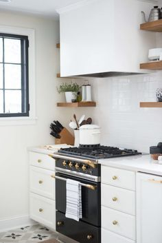 White Kitchen Black Appliances the u-shape layout is practical, while the glass tile backsplash