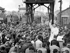 U.S. Army Father (Major) Edward J. Waters, a Catholic Chaplain from Oswego, New York, conducts Divine Services on a pier for members of the first assault soldiers and sailors that will land on the shores of Normandy in a few short hours. Weymouth, Dorset, England, U.K. 6 June 1944.: