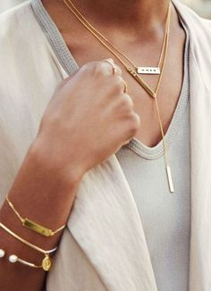 Long golden necklaces, stacked bracelets