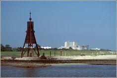 Die Kugelbake ist das Wahrzeichen von Cuxhaven. Im Hintergrund sind Hotels in…