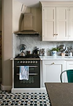 beautiful tile floors, vintage style stove and soft putty gray cabinets