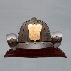 Eight plate iron hoshi -kabuto helmet. In front with a small gilded maedate in the form of uchiwa-fan; four neck-guards (shikoro). The fukikaeshi and neckguards are black lacquered. On a stand. Edo Period. Size;H. including stand: 53 cm. Shipping and handling not included.