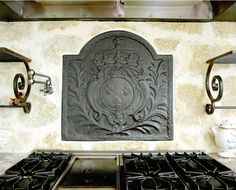 French fireback embedded in limestone behind the stovetop