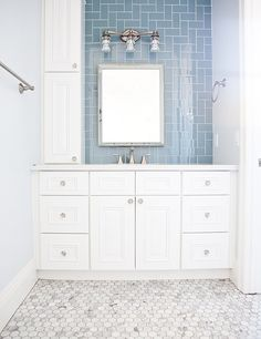 Gorgeous blue subway tile compliments the white cabinetry, polished nickel fixtures and hexagonal marble floor tile in this beautiful bathroom.