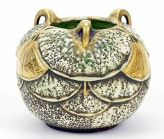 "Ernst Wahliss (Austrian, 1836-1900) A Round Vase. Glazed round earthenware vase bears overlapping kelp decoration with gold decoration. Three handled vase was possibly designed by Paul Dachsel. Underside bears red ""Vienna"" stamp, and numbered ""9773"" Height: 5"""