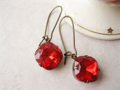 Bright red drop earrings perfect for the holiday season! These dangles feature glass rhinestones in siam red. They are hand set in antiqued