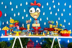 festa galinha pintadinha com mesa de cavalete, parede azul decorada com o personagem de papel, mesa enfeitada com doces temáticos em azul, amarelo e vermelho.