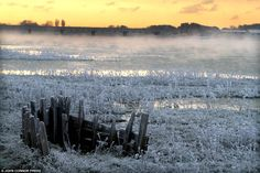 White wonder: An old timber boat carcass sits in the foreground as the sun rises over a hard frost at the estuary of the River Adur in Shoreham