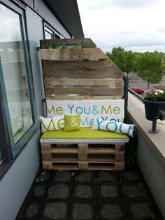 Zelfgemaakte balkon afscheiding met plantenbakje,  bankje en tuinkussens.