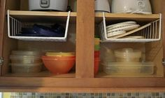 12 Easy Kitchen Organization Tips | Hanging shelf dividers help utilize vertical spaceuse to keep plastic container lids handy