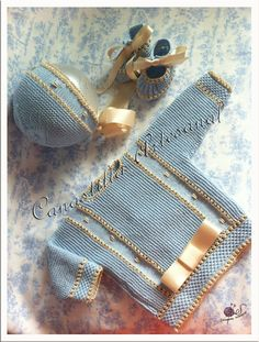 "Baby sweater worked cuff to cuff: garter stitch and stockinette; ""punto de uña"" and embroidered bullion stitch details framing central front panel; ""punto de uña"" and ""punto de escama"" for cuffs and hem (hem picked up after seaming arms and sides); neck, hem and cuffs finished with reverse crochet. ~~ Canastilla artesanal"