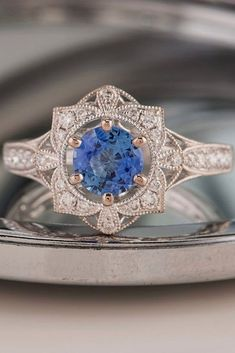 blue colored engagement ring. blue sapphire and diamond engagement ring