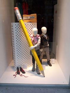 By making the window display props larger than the mannequin children, the eye is instantly drawn to investigate the difference in proportion (principle of design)