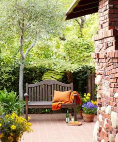"""Layers of greenery and a smooth tile floor play off the rough-textured """"clinker brick"""" and stone of the restored fireplace on this updated front patio"""