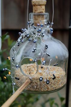 Recycled glass embellished bottle with bead and crystal accents makes this an unique and beautiful bird feeder. Approximately 6 inches high and