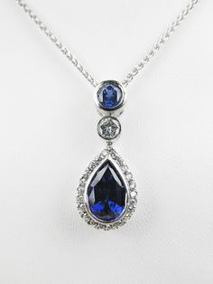 Sapphire and Diamond Necklace with Halo.  Stones are bezel set, and pendant is a slider style.  Made in 18k white gold.  Custom Designed by Redford Jewelers in Salt Lake City, UT