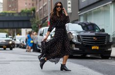 A black printed maxi dress is paired with Acne Studios leather ankle boots, black sunglasses, and a Chloé saddle bag