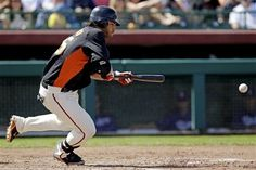 San Francisco Giants' Brandon Crawford gets on base with a bunt single against the Los Angeles Dodgers during the fifth inning of a spring training baseball game