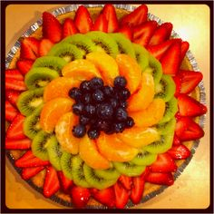 Fruit pudding pie<3 graham cracker crust filled with vanilla pudding topped with various fruits in a spiral decoration.