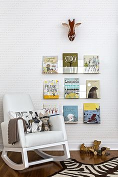 Fabulous boy's nursery features white and gray baby elephants wallpaper, Sissy + Marley Baby Elephant Walk Wallpaper, adorned with faux giraffe head hung over stacked acrylic book ledges situated in front of white rocker, Monte Joya Rocker, paired with Jonathan Adler Zebra Rug.