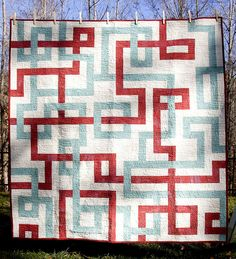Amazing quilt that looks like interconnecting roads. In red/blue on a white background.