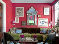 """We wanted a rich and glittering library to play off the cool and airy living room,"" Miles Redd says. The antique rug inspired the vibrant palette. Walls are sheathed in Cuba Libre linen by Stark; the velvet-covered Climate sectional is from Dune. A Venetian mirror reflects a Warhol hanging above a flat-screen TV."