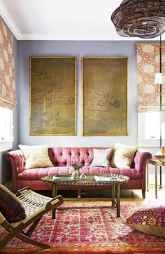 Tufted raspberry sofa in pattern-packed living room with tapestry on wall