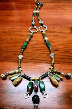"""Stylish Stones $15.00 Free Shipping! 24""""Silver hook clasp. Pretty polished Unakite stones, all in natural shades of brown, green, black, pink, maroon, each with their own unique look and shape. Two hammered silver circles are added to the middle of the necklace accent the earth tones, as well as the silver squares that dangle from the centerpiece stones. Neutral enough to wear with most any color top or dress :)"""