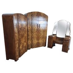 For Sale on 1stdibs - Art Deco bedroom set in a beautiful burr walnut. curved tops to the wardrobe and tallboy, the dressing table with cloud shape mirror. Measures: Wardrobe