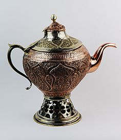Kashmiri Copper Samovar Kettle. This hinged double-lid samovar-like kettle sits on a burner fitted with an internal well into which hot coals can be kept for the purpose of maintaining water in the surrounding chamber hot. The kettle sits on a flared open-work base which enables removal of the ash which has gathered from the coals. Its globular body is embossed and engraved with a frieze of floriform motifs.