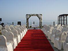 Una alfombra roja y un altar cubierto de rosas blancas, sobriedad y elegancia frente al mar. Club La Cabane Marbella Club, Waterfront Wedding, Sobriety, White Roses, Altars, Floral Decorations, Red Carpet, Lanterns, Elegance Fashion